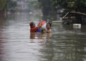 Two woman residents smile as they cross the flood-hit area of Calumpit, Bulacan province, north of Manila, on Wednesday Oct. 5, 2011. Flooding from back to back typhoons have affected more than half a million people in northern Philippines and killed at least 76 people while leaving 29 others missing. (AP Photo/Aaron Favila)