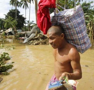 A man carries his belongings in a village hit by flash floods caused by Typhoon Washi in Iligan city, southern Philippines December 19, 2011. Disaster agencies on Monday rushed to deliver body bags, food, water, and medicine to crowded evacuation centres in the southern Philippines as officials considered digging mass graves for hundreds killed in weekend flash floods. (MNS photo)