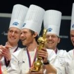 Danish Chef Rasmus Kofoed (2ndL) holds his trophy as he poses with his team after winning the Bocuse d'Or (Golden Bocuse), on January 26, 2011. ©AFP/PHILIPPE MERLE