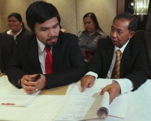 World Boxing Organization welterweight champion and congressman Manny Pacquiao (L) of the Philippines looks at documents shown by his attorney Remigio Rojas during a news conference in Manila March 26, 2012. Pacquiao, vowed to fight to the finish until the final and last round the tax case against him saying it has affected his training for the June welterweight fight against U.S. boxer Timothy Bradley in Las Vegas. REUTERS/Romeo Ranoco (PHILIPPINES - Tags: POLITICS CRIME LAW SPORT BOXING)