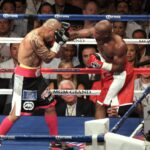 Floyd Mayweather Jr. (right) delivers a right hook to Miguel Cotto's head in this bit of action on his way to a unanimous victory to remain unbeaten in his professional career. Photo: Dr. Ed dela Vega