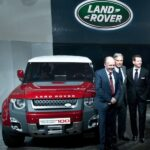Design director Jaguar Iam Cullam (L), Tata Group chairman Ratan Tata (C) and design director Land Rover Gerry Mcgovern (R) pose with the new Land Rover Defender 100 concept car at the 2012 India Auto Expo in New Delhi on January 5, 2012 ©AFP PHOTO/Manan VATSYAYANA