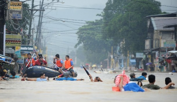 People wade through a flooded street under heavy rains as they are evacuated from their homes in the village of Tumana, Marikina town, in suburban Manila on August 7, 2012, after torrential rains inundated most of the capital. Torrential rains brought the Philippines capital to a standstill on August 7 forcing at least 20,000 people to flee their homes as floodwaters covered half the sprawling city, authorities said. (MNS photo)