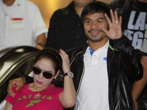 Filipino boxing icon Manny Pacquiao waves beside his wife Jinkee upon his arrival at the Ninoy Aquino International Airport in Manila December 12, 2012.  (MNS photo)