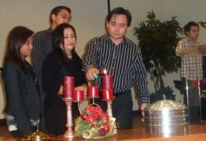 ADVENT AT CORNERSTONE FULLERTON: Willy Lising, Head Deacon of the Cornerstone Christian Fellowship of Orange County, lights the Advent Candle assisted by his daughter, Chloe, Carina (his wife) and son Kenneth (partly hidden) as his eldest son, King, prays at the podium to signal the start of activities to celebrate Christmas in the local Filipino-American Church. Other denominations perform similar tradition as they await the Second Advent.