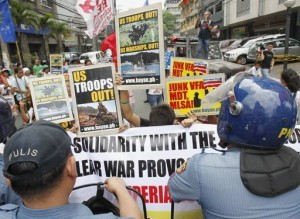 Protesters hold placards in front of anti-riot policemen during a protest calling for the pullout of U.S. troops stationed in the Philippines outside the U.S. Embassy in Manila April 9, 2013. (MNS photo)