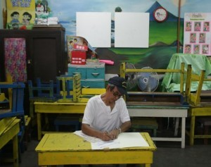 A Filipino man fills out a ballot at a classroom used as a voting precinct during mid-term elections at a school in Manila, Philippines on Monday, May 13, 2013.  (MNS photo)