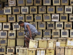 A worker walks on top of a pile ballot boxes after arranging and storing the boxes at a warehouse in Manila April 25, 2013. About 51 million people will cast their votes by using a Precinct Count Optical Scan (PCOS) system for a mid-term election on May 13, a Commission on Elections (COMELEC) said. (MNS photo)