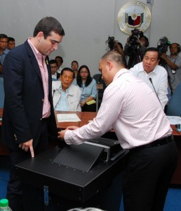 "SMARTMATIC-TIM MACHINE DEMO: Senate President Juan Ponce Enrile and Senate Blue Ribbon Chairman Richard Gordon watch closely as Smartmatic-TIM sales director Cesar Flores (left) and technical support manager Miguel Avila (right) demonstrates the machine that will be used in the automation of 2010 polls during a Senate committee hearing today, July 6. ""We can no longer stop automation if it can be done. The only thing that we are saying is yes, we will automate but we must not rely fully on automation because there is a possibility, although remote, that it may not work"", Enrile said. (Photo courtesy of www.senate.gov.ph)"