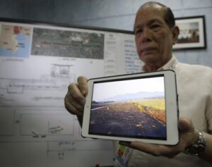Civil Aviation Authority Deputy Director General John Andrews displays a photo from his notepad showing the grass that spilled on the runway, indicating the landing made by a Cebu Pacific Airbus A320 passenger plane which overshot the runway Saturday at Davao city International Airport in southern Philippines, during a news conference Tuesday, June 4, 2013 in Manila, Philippines. Philippine aviation authorities said Tuesday they were investigating Cebu Pacific pilots and crew who left passengers waiting some 15 minutes before deploying emergency slides on the plane that overshot the runway and landed on its nose.  (MNS photo)