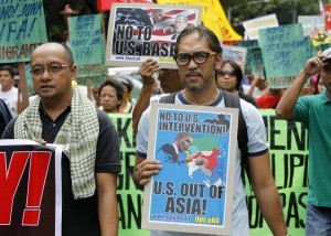 Protesters display placards and banners as they march towards the gates of the U.S. embassy during a protest in Manila July 4, 2013. About 300 activists marched on the streets on Thursday to denounce plans to grant U.S. troops access to a proposed new naval base which they say undermines Philippine sovereignty.  (MNS photo)