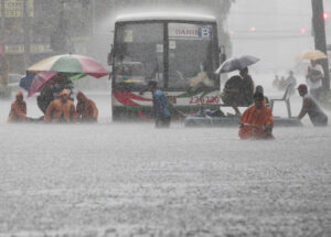 Office workers cross a flooded street using makeshift floats during heavy rain at the financial district of Makati, south of Manila, Philippines on Tuesday, Aug. 20, 2013. Flooding caused by some of the Philippines' heaviest rains on record submerged more than half the capital Tuesday, turning roads into rivers and trapping tens of thousands of people in homes and shelters. The government suspended all work except rescues and disaster response for a second day. (MNS photo)