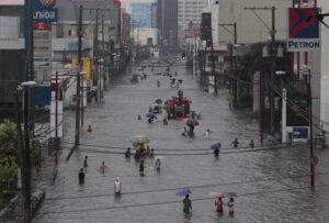 Filipinos wade through a flooded street at the financial district of Makati, south of Manila, Philippines on Tuesday, Aug. 20, 2013. Some of the Philippines' heaviest rains on record fell for a second day Tuesday, turning the capital's roads into rivers and trapping tens of thousands of people in homes and shelters. The government suspended all work except rescues and disaster response. (MNS photo)