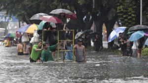Office workers stand on top of a rolling scaffolding as they cross a flooded street at the financial district of Makati, south of Manila, Philippines on Tuesday, Aug. 20, 2013. Flooding caused by some of the Philippines' heaviest rains on record submerged more than half the capital Tuesday, turning roads into rivers and trapping tens of thousands of people in homes and shelters. The government suspended all work except rescues and disaster response for a second day. (MNS photo)