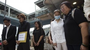 Tse Chi-hang (2nd L) and Lee Mei-chun (R), family members of tour guide Masa Tse, who was killed during Manila's bus hostage crisis in 2010, lawmaker James To Kun-sun, and survivor Yik Siu-ling (2nd R) observe a moment of silence outside the Philippine Consulate in Hong Kong August 23, 2013. Survivors and family members of the victims of the Manila bus hostage crisis have filed writs in the High Court in Hong Kong to seek compensation from the Philippines. The group is taking legal action after claiming Manila has ignored demands for compensation and an official apology since the tragedy, according to a government radio report.  (MNS photo)