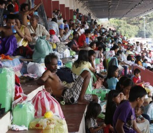 Displaced residents rest in a stadium turned into an evacuation centre in Zamboanga city in southern Philippines September 18, 2013. Police said about 80 percent of the city was retaken and rebels contained in two villages, while death toll in fighting reached 106 people and displaced around 109,000.  (MNS photo)