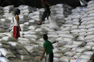 A worker passes a sack of rice to other workers inside a National Food Authority (NFA) warehouse in Taguig City, south of Manila March 26, 2012. The Philippines is close to signing a government-to-government rice supply agreement that would make Cambodia a potential supplier of the grain staple to Manila, along with Vietnam and Thailand, agriculture officials said on Monday.    REUTERS/Cheryl Ravelo (PHILIPPINES - Tags: AGRICULTURE BUSINESS POLITICS)