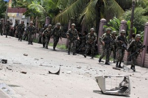 Security forces walks past debris scattered on a street after rebels from the Moro National Liberation Front (MNLF) clashed with government troops in Zamboanga city, southern Philippines September 9, 2013. Rebels took 30 civilian hostages in the southern Philippines on Monday and held security forces in a standoff as part of a drive to derail peace talks, officials said. Police commandos cordoned off parts of Zamboanga City on the island of Mindanao after a rogue faction of the Moro National Liberation Front (MNLF) took hostages and tried to march to the city hall to raise their flag, an army commander said.(MNS photo)
