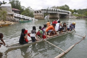 Villagers ride on a boat to cross a river after a bridge was damaged in Loon, Bohol, a day after an earthquake hit central Philippines October 16, 2013.  (MNS photo)