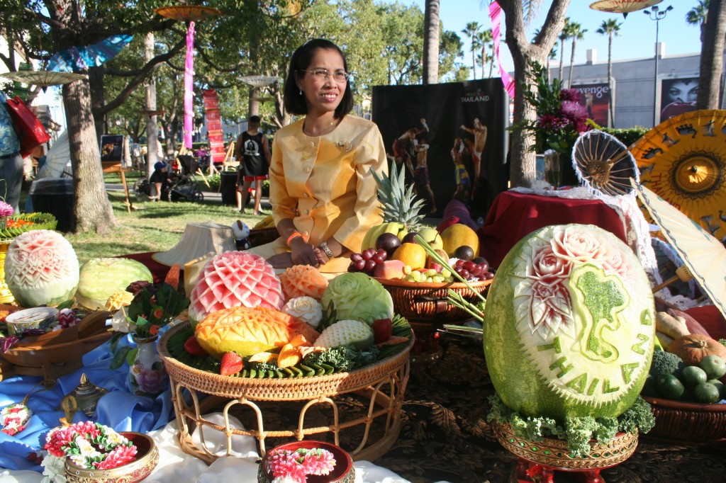 A map of Thailand is engraved in the watermelon as a Thai lady proudly displays sculptures of food art at the festival.