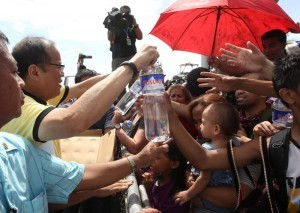 President Benigno S. Aquino III personally distributes water to the families displaced by Super Typhoon Yolanda (Hainan) at the evacuation center during his visit to the province of Leyte to assess the extent of damage in the area on Sunday (November 10). Typhoon Yolanda is the world's most poerful typhoon in 2013. (MNS photo)