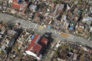 An aerial view shows signs for help and food amid the destruction left from Typhoon Haiyan in the coastal town of Tanawan, central Philippines, Wednesday, Nov. 13, 2013. Typhoon Haiyan, one of the strongest storms on record, slammed into six central Philippine islands on Friday leaving a wide swath of destruction and thousands of people dead. (MNS photo)
