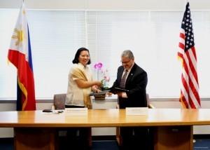 Consul General De La Vega (left) exchanging the Cooperative Agreement with Regional Administrator Rosales.
