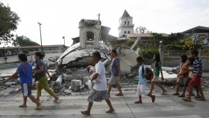 Residents walk past a destroyed church belfry in Tubigon, Bohol , a day after an earthquake hit central Philippines October 16, 2013.  (MNS photo)