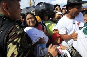 A woman and her child plead from the frantic crowd to be prioritized on an evacuation flight in Tacloban, central Philippines, Thursday, Nov. 14, 2013. Typhoon Haiyan, one of the most powerful storms on record, hit the country's eastern seaboard on Friday, destroying tens of thousands of buildings and displacing hundreds of thousands of people.  (MNS photo)