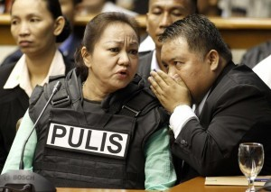 Janet Lim Napoles, wearing a bullet proof vest, listens as her lawyer Howard Areza whispers to her while Napoles attended a public inquiry at the Senate in Manila November 7, 2013. Napoles, the wife of a former Marine major, has been accused by the Department of Justice of setting up fake non-government organisations that since 2007 received lawmakers' pork barrel funds and then routed the money back to them.