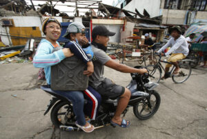 Survivors of Typhoon Haiyan carry fuel, which they bought at double the regular price, on a motorcycle in the typhoon devastated town of Palo, near Tacloban November 16, 2013.  (MNS photo)