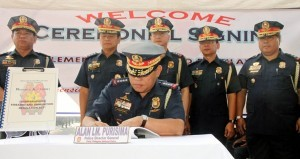 Philippine National Police Director General Alan Purisima signs the Implementing Rules and Regulation (IRR) of Republic Act No. 10591 or the Comprehensive Law on Firearms and Ammunition during the flag-raising ceremony on Monday (Nov. 25, 2013) at the PNP Headquarters in Camp Crame, Quezon City. Purisima said the IRR of the new gun law will enable the PNP to curb down gun-related crimes and establish effective firearms control in the land. (MNS photo)