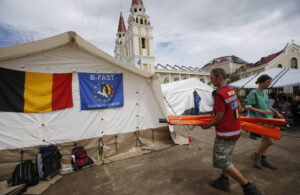 A member of the Belgian state rapid reaction unit, the Belgian First Aid and Support Team (B-FAST), carries tent poles at a makeshift hospital, jointly set up with German NGO International Search and Rescue (ISAR-Germany), for Typhoon Haiyan victims in the yard of the Metropolitan Cathedral of the Archdiocese of Palo, near Tacloban in central Philippines November 16, 2013. (MNS photo)