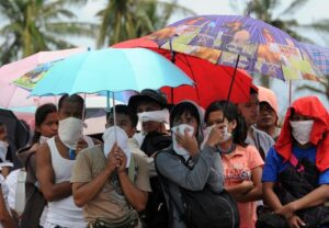 Residents cover their noses because of the smell of rotting corpses, as they queue for free mobile phone power charging at the city hall in Tacloban, Leyte province in central Philippines, on November 14, 2013 (MNS photo)