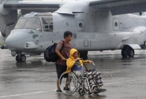 An elderly survivor evacuated from the disaster zone of typhoon Haiyan is wheeled past a V-22 Osprey on tarmac after arriving on a military plane at Villamor Air Base in Manila November 13, 2013. Philippine officials have been overwhelmed by Haiyan, one of the strongest typhoons on record, which tore through the central Philippines on Friday and flattened Tacloban, coastal capital of Leyte province where officials had feared 10,000 people died, many drowning in a tsunami-like wall of seawater. (MNS photo)