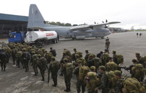 Philippine soldiers walk near a military C-130 plane as they prepare to go to Tacloban city, at the Villamor Airbase, in Manila, Philippines on Tuesday, Nov. 12, 2013. Four days after Typhoon Haiyan struck the eastern Philippines, only a trickle of assistance has made it to affected communities. Authorities said at least 9.7 million people in 41 provinces were affected by the devastating typhoon.  (MNS photo)