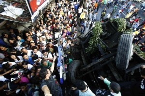 Pedestrians walk beside an overturned bus lying along a busy street at Bicutan after the bus fell off an elevated expressway and crashed into a van below in Taguig city, south of Manila December 16, 2013. At least 21 people were killed during the incident, according to the police. (MNS photo)