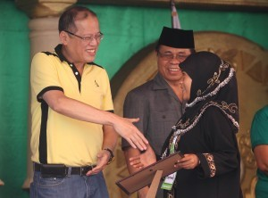 "President Benigno S. Aquino III distributes vouchers for Scholarship Grants to beneficiaries during the Ceremonial Launch of Sajahatra Bangsamoro Program: Peace Dividends of the Framework Agreement on the Bangsamoro (FAB) at the Bangsamoro Leadership and Management Institute (BLMI) in Barangay Salimbao, Sultan Kudarat, Maguindanao on Monday (February 11, 2013). The strong partnership between the government (GPH) and the Moro Islamic Liberation Front (MILF) has become more evident as both sides work together in the process of identifying beneficiaries and their immediate needs that will be addressed by the Sajahatra Bangsamoro program. The FAB indicated that ""the Parties agree to intensify development efforts for rehabilitation, reconstruction, and development of the Bangsamoro, and institute programs to address the needs of MILF combatants, internally displaced persons, and poverty-stricken communities."" In photo is MILF chairman Al Haj Murad Ebrahim. (Photo by: Ryan Lim / Malacañang Photo Bureau)."