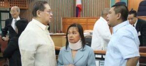 Former Philippine President Gloria Macapagal Arroyo, now a sitting lawmaker in the lower house of Congress, is flanked by husband Jose Miguel Arroyo (L) and her son Congressman Juan Miguel Arroyo inside  the Sandiganbayan anti-graft court in Quezon City, Metro Manila, April 11, 2012. Arroyo  entered a plead of not guilty before an anti-corruption court for her role in an aborted $329 million broadband deal with China's ZTE Corp in 2007 after a congressional inquiry in 2008 showed she allegedly did not stop her allies from collecting huge pay offs for the deal. Arroyo's husband, a former communications minister and the former head of the country's elections agency are facing similar corruption charges. REUTERS/Renz Joshua Posedio/ Philippine National Police-Public Information Office/Handout