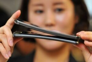 A South Korean promoter shows LG Electronics' curved-screen smartphone G Flex. The handset flexes so that the display doesn't break when dropped or accidentally sat on. ©AFP PHOTO / JUNG YEON-JE