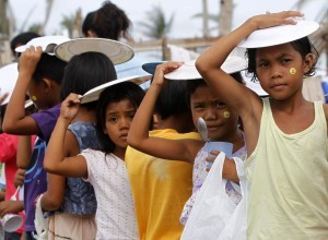 Children hold plates on top of their heads against rainfall as they queue for free meals during Christmas celebrations at the town of Bislig, Tanauan in Leyte province, central Philippines December 24, 2013, a month after Typhoon Haiyan battered central Philippines. The Philippines has warned that predators might prey on Yolanda victims. (MNS photo)