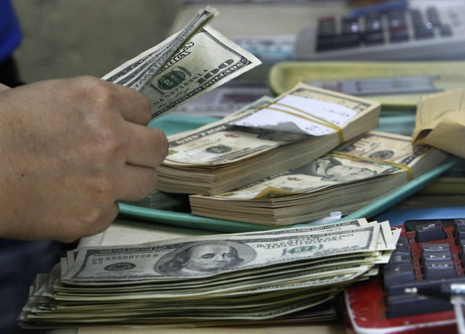 An Employee Counts U S Dollar Bills Before Changing It To Philippine Pesos Inside A Money Changer