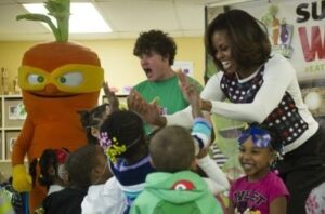 "First Lady Michelle Obama (C) ""high-fives"" children with the Super Sprowtz and ""super hero"" trainer Roger Hanson (L) during a visit to La Petite Academy childcare center in Bowie, Maryland, February 27, 2014, as part of the Let's Move! Campaign. ©AFP PHOTO / Jim WATSON"
