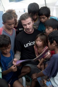 "With a UNICEF shirt on, football superstar David Beckham reads to young Filipino children during his visit to the devastated city of Tacloban on Thursday. This iconic shot was posted on Michael Beckham Facebook page, which he personally ""liked."""
