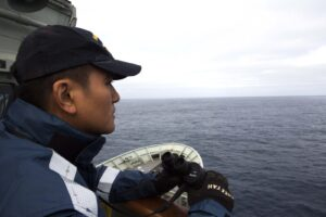 March 24, 2014 – Able Seaman Januario Callos keeps watch on the starboard bridge-wing of HMAS Success during the search for the missing Malaysia Airlines Flight MH370. The supply ship will use visual lookouts and is equipped with radar and communications equipment to support a coordinated search with other assets within the area. With a displacement of 18 thousand tonnes and carrying a crew of 218, HMAS Success is one of the RAN's largest vessels, capable of providing a valuable surface search, investigation and recovery capability to support the ADF air operations. Photo: LSIS James Whittle aboard HMAS Success/Commonwealth of Australia, Department of Defence