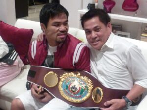 "MANNY PACQUIAO IN A LIGHT MOOD: Manny Pacquiao ""reacts"" to Realtor Nick Enciso being photographed with his championship belt at his Los Angeles home. The boxing hero flew in Saturday from the Philippines to prepare for his second encounter with Tim Bradley on April 12 in Las Vegas."
