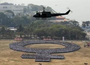 A helicopter hovers above a large human women symbol at the Quirino Grandstand on the celebration International Women's Day in Manila, the Philippines, 08 March 2014. According to the Philippine Commission on Women, more than 10,000 participants join the human formation to set a new Guinness World Record as the 'Biggest human formation on women's symbol'.  (MNS photo)