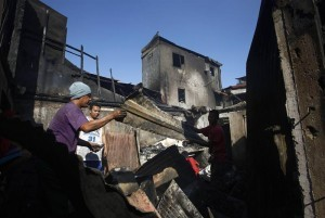 A Filipino collects salvageable materials among debris following an overnight fire that razed a slum area in Manila, Philippines, 05 April 2014. According to the Bureau of the chief fire inspector, around 100 houses were destroyed at a shantytown leaving more than 200 families homeless. (MNS photo)