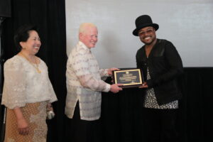 Jose L. Cuisia, Jr. hands out a plaque of appreciate to Filipino-American artist Apl.de.ap.