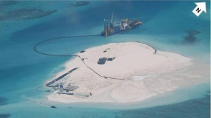 In this photo taken Feb. 25, 2014 by surveillance planes and released Thursday, May 15, 2014, by the Philippine Department of Foreign Affairs, a Chinese vessel, top center, is used to expand structures and land on the Johnson Reef, called Mabini by the Philippines and Chigua by China, at the Spratly Islands at South China Sea, Philippines. The Philippines has protested China's reclamation of land in the disputed reef in the South China Sea that can be used to build an airstrip or an offshore military base in the increasingly volatile region, the country's top diplomat and other officials said Wednesday, May 14, 2014. The white arrow was added by the source. (MNS photo)
